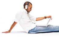 Man listening to a podcast with headphones on a laptop.