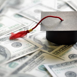 College graduation cap on top of money for student loans