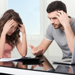 Upset couple after looking at bank statement.
